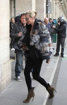 Kate Moss showed off her signature style in a fur coat, skinny black jeans, and olive booties. See more at www.HerStyledView.com