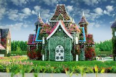 A fantasy flower house at the Miracle Garden, which has plants growing over its turrets, d...