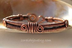 This copper bracelet is full of textures. Two coiled wires have five stations of wrapped wires with spiraled ends and a hand forged spiral clasp secures the bracelet on the wrist. The copper has a p