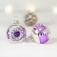 To søde julekugler i blank sølv, mat lilla og hvid.  Størrelse på julekuglerne er ca. 4,5 cm incl. krave. Mundblæst glas der er hånddekoreret. Produceret hos et tysk familiefirma.