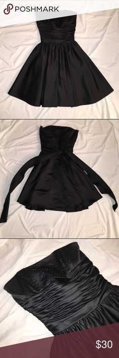 Black Corset Dress Beautiful black dress with a ruched, corset-like bodice and a beaded bust. Two of the small beads have fallen off but it isn't noticeable. The fabric is very thick and satiny. Gently used and 100% polyester. eden maids Dresses Strapless