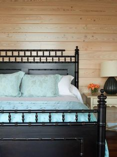 Black antique headboard and footboard, aqua linens, pine paneled walls in this pretty coastal beachy bedroom Plywood Headboard, Headboard And Footboard, Headboards, Bald Head Island Nc, Antique Headboard, Painted Beds, Striped Chair, Going Bald, House Of Turquoise