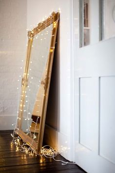 simple mirror w/ christmas lights on hardwood floor #Anthropologie #PinToWin