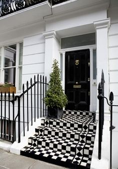 27 Pictures of Black Front Doors (Front Entry) Standing over a vibrant checker patterned set of steps, this black door features a plethora of subtle brass hardware, framed in smoked glass. Front Stairs, Front Entry, Black Front Doors, London Townhouse, Black And White Tiles, Black White, White Walls, Front Door Design, White Houses