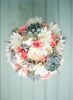 bridal bouquet comprised of white dahlias, ivory garden roses, silver brunia, white heather, gray dusty miller, peachy pink spray roses and blue-green succulents wrapped in ivory ribbon with the stems showing