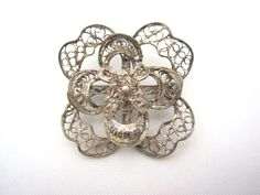 A beautiful vintage brooch. Its silver filigree in intricate swirls. These are usually sterling silver, but I cannot find the mark. (Usually