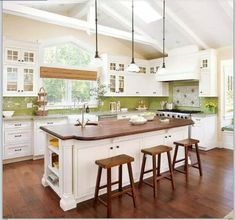 White kitchen with dark floor and wooden island counter, similar stools