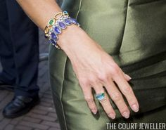 On her right wrist, Maxima wore three bracelets: her diamond wedding bracelet, the gold and cabochon gemstone bracelet inscribed with her family's names, and a bracelet made of blue gemstones.