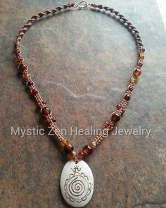 Tibetan Pendant with Agate Beads ~ Hand carved Tibetan yak horn pendant with Agate beads. The Tibetan om & spiral symbolize inner peace through inner strength.