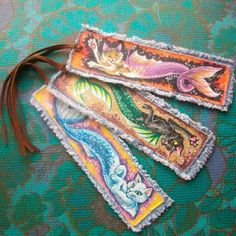 These bookmarks, or tags, or ribbons, are made from scrap denim and leather. I used the denim like a canvas, to paint the scenes onto.