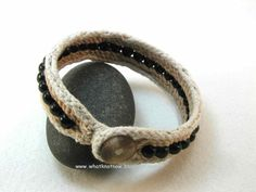Slender and dark this hand assembled fabric cord bracelet adds a touch of casual class to your day.  It features a row of wood beads with a stirrup loop and button toggle closure. Flexible, comfortable and stylish this handmade cuff layers nicely with your bracelet collection or wear alone for an understated look. One in size large with black beads  8 1/2 (219 mm) inside circumference when closed 2 5/8 (67 mm) inside diameter 7/8 (22 mm) wide  One in size medium with dark brown...