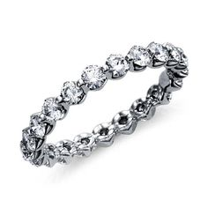 This exquisite diamond eternity ring features diamonds hand-set in a unique and low-profile platinum setting.