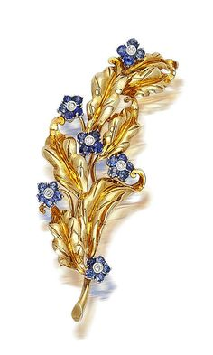 An eighteen karat gold, sapphire and diamond brooch, Cartier, circa 1960  designed as six floral clusters of single-cut diamonds and circular-cut sapphires, accentuated by gold leaves; signed Cartier; length: 3in.