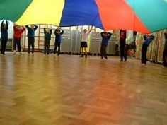 Use parachute to teach Spatial Concepts.  Children learn spatial concepts first by physically being in the space.  Teach: On top, under, around, next to, beside, through, over.   You can also use to teach basic adverb vocabulary to describe the movement of the parachute.