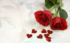 Обои Две красные розы лежат на белой драпировке, рядом мармеладные красные сердечки