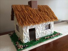 white frosting, whole wheat (brown) spaghetti for thatched roof look, wax paper and toothpick windows, dried beans for stones. White Gingerbread House, Gingerbread House Designs, Gingerbread House Parties, Gingerbread Houses, Christmas Bells, Christmas Holidays, Xmas, Cookie House, Irish Cottage