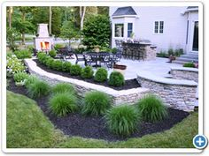 Raised bluestone patio featuring circular steps, sitting walls, outdoor kitchen and fieldstone fireplace