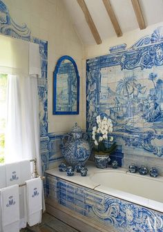A panel of circa-1730 Dutch scenic tiles decorates the wall above a Victorian tub in the bath of an English country estate.