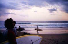 Un grupo de surfistas se prepara para meterse en el océano.