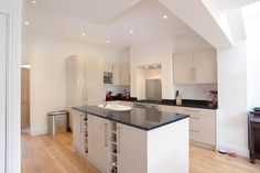 Brockley, SE4, Side Return Extension, Side Extension, Victorian Terraced House, Bi-Fold Doors, Pitched Roof, Roof Lights, Kitchen, Kitchen Extension Ideas, Red Wall, Contemporary Kitchen, Wood Flooring, Dark Countertop
