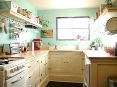 For the new kitchen: cream cabinets, green walls. Shelves above the stove with bars.