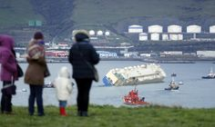"""Varias personas observan el carguero """"Modern Express"""", que se encontraba a la deriva en el Golfo de Vizcaya tras sufrir una fuerte escora, entrando remolcado al puerto de Bilbao. El mercante se encuentra desde las 5 de la tarde dentro del puerto y va en"""