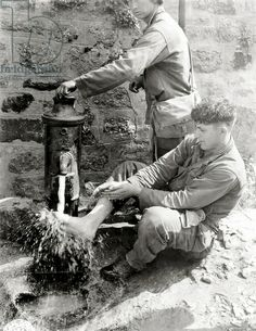 Private C. L. Scott of the 4th Infantry Division is washing his feet at a public fountain, Villedieu-les-stoves, Normandy, France, 2nd August 1944
