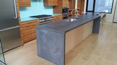Gray stained concrete countertop with waterfall legs