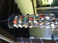DIY Bottle cap wind chime. Bottle caps, jump rings, small eye hooks, and a 99 cent frame from Michaels.  It sounds like the rain!