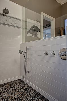 Clean and classic shower design in white, with unique stone flooring.  From a 4-story Craftsman style home construction by Lavallee Construction, discovered on Porch.com