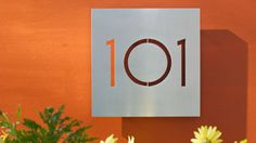Modern House Numbers also does round or square plaques with cut out stencil numbers or letters.  Steel, black, or white.