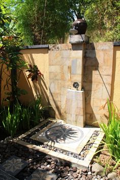 Stand-alone outdoor shower with plenty of small rocks. Follow rickysturn/home-styling