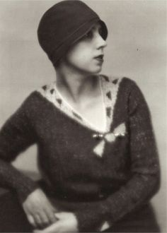 In the 1930s Elsa Schiaparelli designed some gorgeous trompe l'oeil sweaters featuring various bows, collars and ties knitted into the sweater.