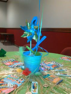 summer party centerpiece.  bucket with sand, pinwheel, shovel and balloons tied to the handle. cute!