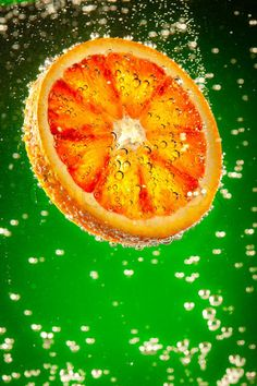 'fresh orange falls in water on a green background'