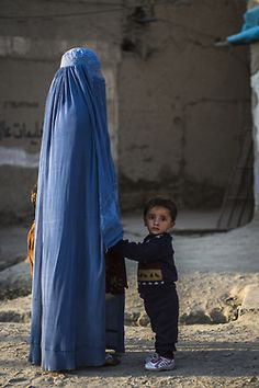Daily Life In Kabul    A young Afghan boy looks on as his hand is held roadside by a woman wearing a burqa in Kabul, Afghanistan.