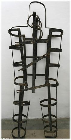 This is a medieval torturer device known as the Coffin. The offender would be put inside this and locked up and the coffin would be hung from a tree or the city walls. Usually the convict inside would die of thirst, exposure, or hunger. This torturer device is similar to Tilman's iron harness as it was a torture for him to be inside this because it prevented him to be free and to be able to roam around as it was his nature to do so. - Chris