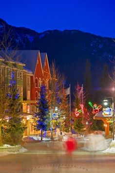 An attractive night scene along the pedestrian only path called the Village Stroll in Whistler, BC. Coloured lighting draped decoratively on trees liven up a cold winter evening as visitors stroll the quaint village.