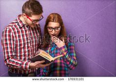 young couple in clothes and stylish hipster glasses reading a book. studio shot