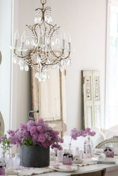 Love the elegance of a chandelier pared with rustic farm furniture. So cool.