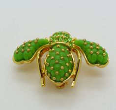 "Joan Rivers Quilted Enamel Green Bee Brooch Pin. Set in gold tone metal. Signed Joan Rivers. Includes Original box and Pouch. Measures 1 4/8"" by 1 1/8"" Excellent condition."