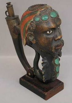 """Pipe, carved wood, Louis XV period, Paris, France. 10 1/2 h.    Head of African type man with jade decorating stones in copper settings and trim, and painted in red and green, eyes are ivory; markings, 'Pipe Enseigne du Marchand de Tabac Au Nabab Paris Epoque Louis XV'     A handwritten note in French attached to the bottom of this pipe makes it likely that this pipe was used in a tobacconist's store, called, """"Au Nabab.""""    Courtesy of the Colorado Springs Pioneers Museum"""