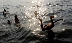 A young Indian boy dives in the Arabian sea water in Mumbai, India, on March 7. (Rajanish Kakade/Associated Press)
