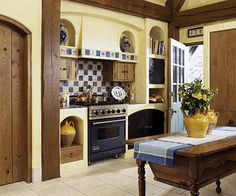 Earthy and Elegant From hand-finished hardware to hand-painted tiles, this kitchen captures a sense of natural artistry. Noticeably absent from the kitchen are upper cabinets. But an antique bread cabinet serves as storage. The unit maintains the country-French style created by details installed throughout the kitchen, such as plaster finishes and blue and yellow accents.