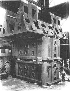 """the """"Fifty"""", a massive press forge that presses foot-thick chunks of raw metal into precise airplane and engine parts in a single 50,000-ton stroke. note the man standing next to it for scale"""