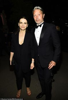 Androgynous chic: French actress Juliette Binoche put on a busty display in a black suit a...
