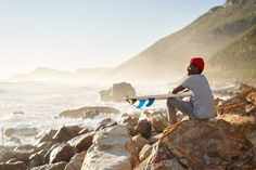 A surfing lifestyle image of a young Black surfer sitting whilst watching the surf after surfing Styled by Bielle Bellingham Photographer: Micky Wiswedal Model: Mandla Ndlovu Young Black, Surf Style, Surfing, Waves, The Unit, Stock Photos, Lifestyle, Model, Image