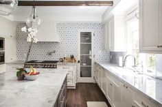 white-marble-countertops-gray-flower-mosaic-tile-backsplash _ Love this fresh kitchen with an accent wall of Walker-Zanger tile - photo: Bethany Nauert