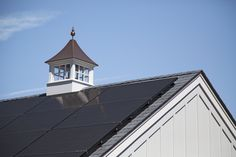 On the south-facing slope of the garage roof,  high-efficiency black photovoltaic panels by sunbugsolar.com should provide a third of the house's energy. A cupola in PVC and copper by RoyalCrowneOutdoorAccents.com gives it farmhouse appeal.