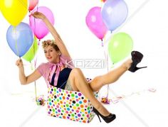 smiling young woman holding a balloon and sitting in a box. - Portrait of a smiling young woman holding a balloon and sitting in a box over white background, Model: Carrie Galbraith